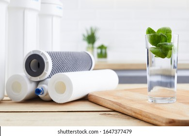 A glass of clean water with osmosis filter and cartridges in a kitchen interior. Concept Household filtration system.