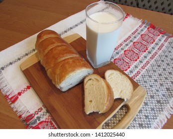Glass of clear glass filled with kefir, homemade loaf and slices of loaf lying on the table.