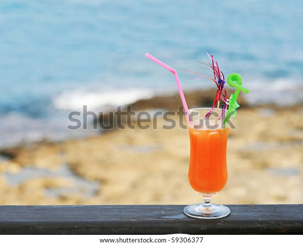 Glass of cocktail against sea and coastline standing on wooden rails of cafe  veranda. Ready to drink mango juice with straws and decorations.