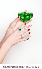 Glass with a cocktail from the female hands. Green drink with ice. Precious rings on the fingers.