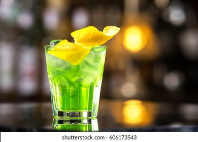 Glass of cocktail green fairy with lemon and absinthe at bar stand festive background.