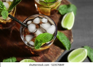 Glass of cocktail with ice on wooden cutting board closeup