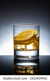 Glass of cocktail with ice-cubes and lemon, isolated