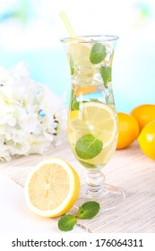 Glass of cocktail with lemon and mint on table on light blue background