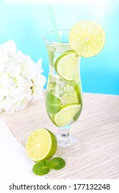 Glass of cocktail with lime and mint on table on light blue background