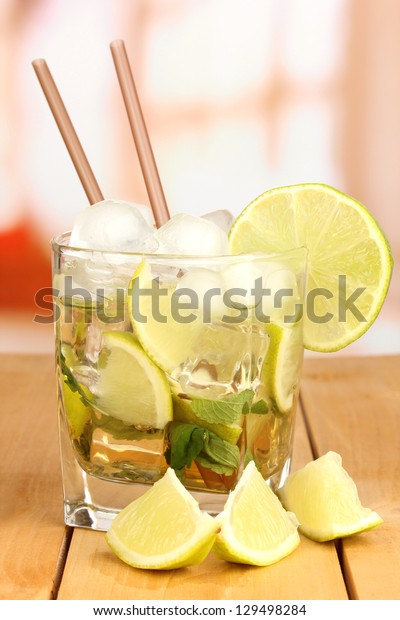 Glass of cocktail with lime and mint on wooden table on bright background