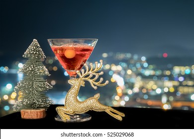 A glass of cocktail margarita or rose wine with bottle of decoct over light city blurred background, Christmas festive celebration. End of the year, Welcome to New Year 2020. Good long holiday start.