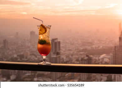 Glass of Cocktail Punch on Balcony with Sunset City View in the Background