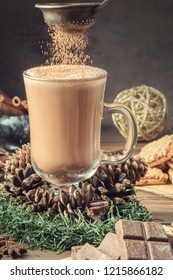 Glass cocoa mug or coffee with milk froth on wooden table served cookies cinnamon chocolate and winter holiday accessories. New Year Christmas card. Hand pours of cocoa powder.