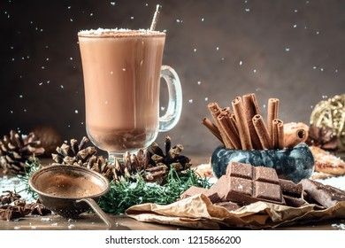 Glass cocoa mug or coffee with milk froth on wooden table served cookies cinnamon chocolate and winter holiday accessories. New Year Christmas card.