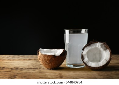 Glass of coconut water with nut on wooden table
