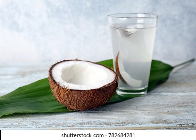 Glass of coconut water with nut on wooden background