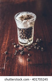 Glass with coffee beans and milk foam