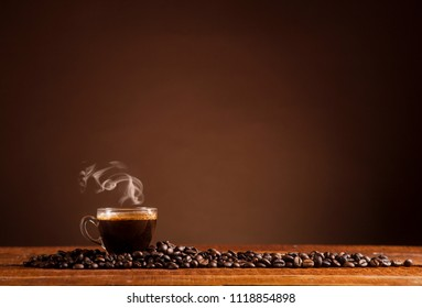 Glass coffee cup and coffee beans on old wooden table and brown background with copy space