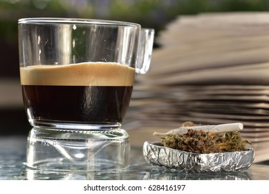 glass coffee cup with coffee foam , cannabis joint, cannabis ground buds and book on glass table top on balcony