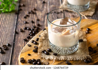 Glass of Coffee Irish Cream Liqueur with coffee beans on wooden background. Beverage photography