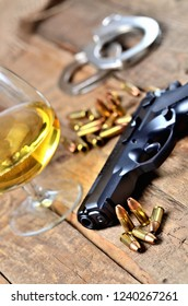 Glass of cognac, 9mm pistol, handcuffs and bullets on old wooden table - vertical photo
