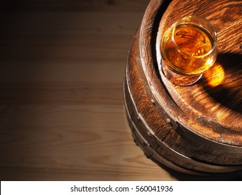 Glass of cognac with barrel on wooden background.