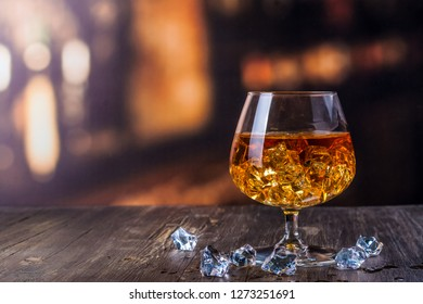 Glass of Cognac and blured bar background