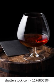 Glass of cognac brandy drink with black coaster on top of wooden barrel on black background.