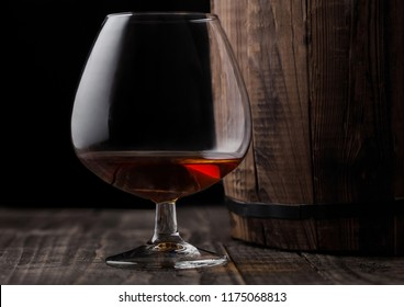 Glass of cognac brandy drink next to wooden barrel on black background.