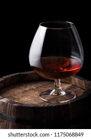Glass of cognac brandy drink on top of wooden barrel on black background.