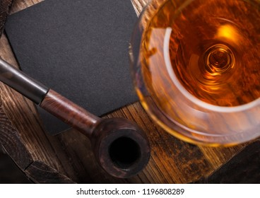 Glass of cognac brandy drink and vintage smoking pipe on top of wooden barrel on black background.