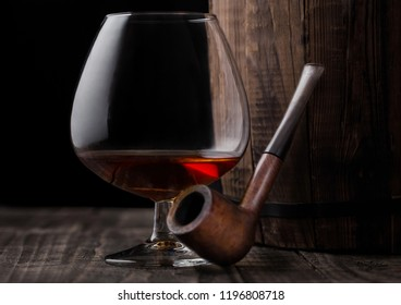 Glass of cognac brandy drink and vintage smoking pipe next to wooden barrel on black background.