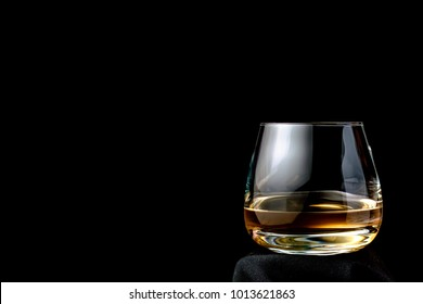 The glass of cognac or brandy isolated on a black background. Place for your text.