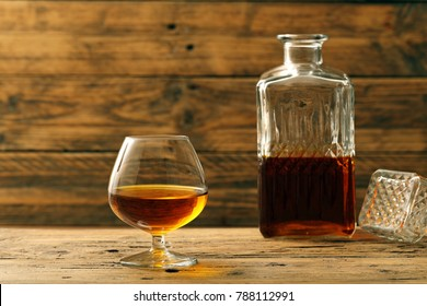 a glass with cognac or brandy on rustic background