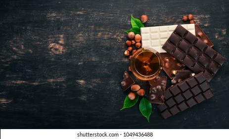 A glass of cognac, brandy, whiskey and a set of chocolate with cookies and sweets. On a black wooden background. Copy space for text.