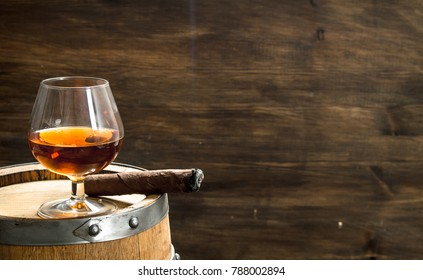 glass of cognac with a cigar on a barrel. On a wooden background.