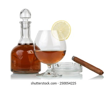 Glass of cognac with cigar on white background