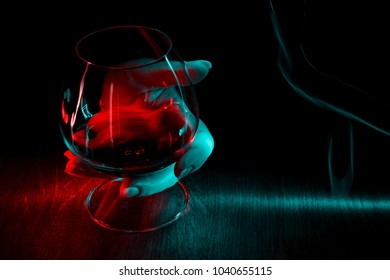 A glass of cognac in hand on dark background.