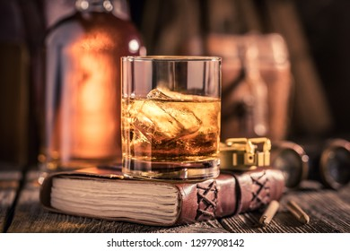 Glass of cognac with ice and golden bottle