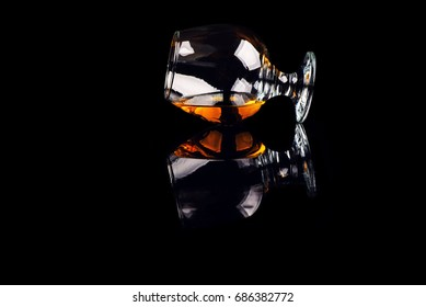 glass with cognac on a black background