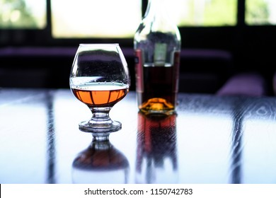 A glass of cognac on a black table with a bottle of cognac in the background.