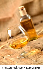 Glass of cognac on rustical wooden background and bottle in background vertical photo