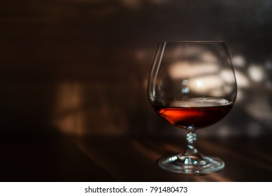 Glass of cognac on the table on the right side with sun rays. Alcohol concept background
