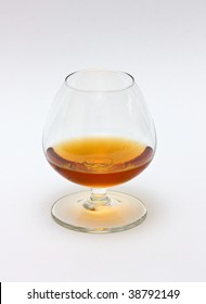 A glass of cognac on white background.