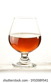 A glass of Cognac over a white background.