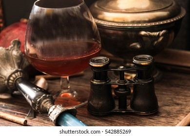 glass of cognac with stained binoculars and blue candle on a wooden background