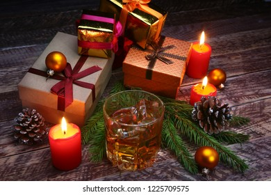 Glass with cognac or whiskey, Christmas balls and candles. New Year's tree, balls and glass with alcohol.