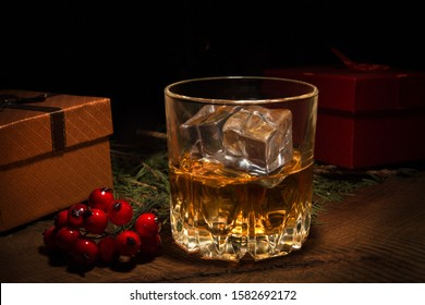 Glass with cognac or whiskey, Gift box and Christmas balls. New Year's tree. Happy holidays decoration.