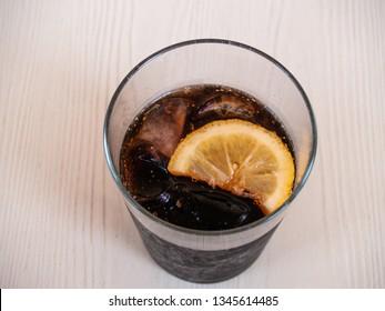 A glass of coke with a slice of lemon