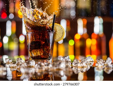 Glass of cola drink on bar counter with ice cubes and splash