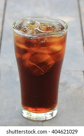 glass of cola with ice cubes on wood table.