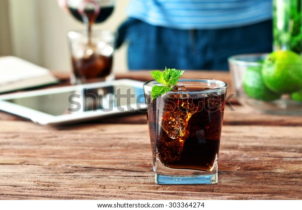 glass of cola with ice and mint on a wooden background. On the background of men hands pouring cola in beaker. Close up. Free space for text. Selective focus. Copy space
