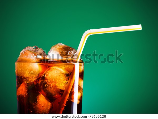 glass of cola with ice and straw on green background