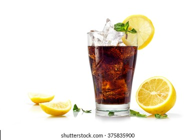 glass of cola, ice tea or coke with cubes, slices of lemon and peppermint garnish, isolated on white